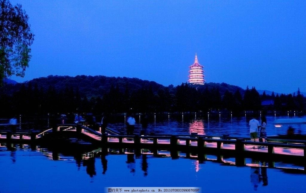杭州 西湖 夜景 湖面 游船 湖堤 游客 小桥 树木 低矮山丘 雷峰塔